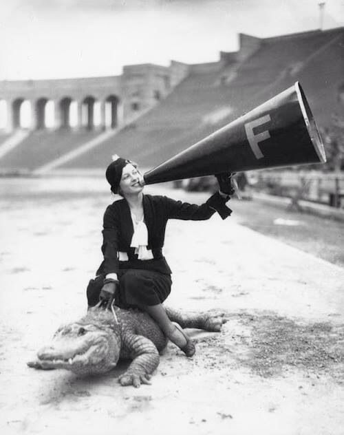 Vintage black and white photo of a woman sitting on an alligator in a sports stadium shouting through a megphone, Los Angeles 1930's via LA Public Library
